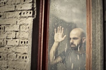 man leaning on window